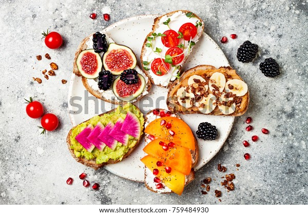 Healthy breakfast toasts with peanut butter, banana, chocolate granola, avocado, watermelon radish, persimmon, pomegranate, chia seeds, tomato, figs, blackberry.