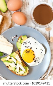 Healthy breakfast - toasts from rye bread with avocado, cheese and egg on a white wooden background. Top view. Flat lay