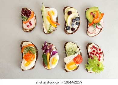 Healthy breakfast toasts with vegetables, fruits , meat and microgreen on concrete background. Clean eating healthy food concept. Top view. Copy space.