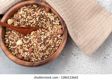 Healthy breakfast, vegan vegetarian granola made of green buckwheat with nuts and pumpkin seed in wooden bowl