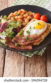 Healthy breakfast: waffle sandwich with egg, bacon, beans and salad close-up on a plate. Vertical