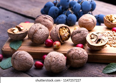 healthy breakfast - wheat, oatmeal, cranberries, nuts, grapes on a wooden table