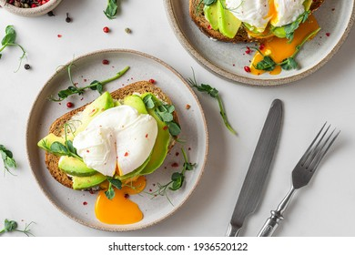 Healthy breakfast. Whole wheat toasted bread with avocado, poached egg, soft cheese and sprouts on white background. top view. Healthy diet food
