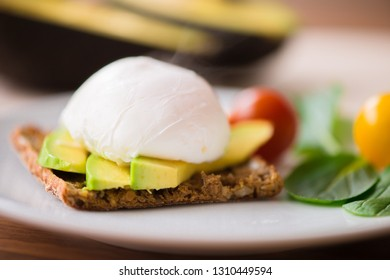 Healthy breakfast with wholemeal bread toast and benedict eggs with green salad and avocado