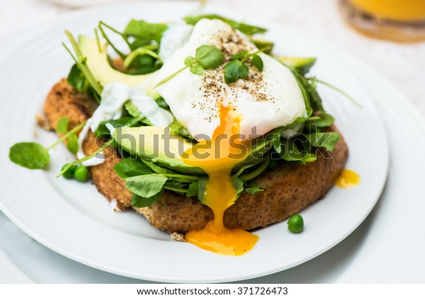Healthy Breakfast with Wholemeal Bread Toast and Poached Egg with Green Salad, Avocado and Peas. Orange Juice and Orange Slices on the Background.