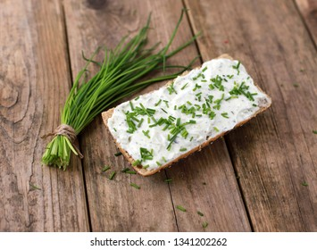 healthy breakfast -  wholemeal roll with quark and fresh chives on a rustic wooden table