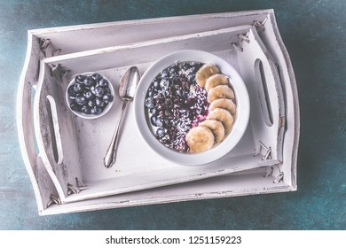 healthy breakfast yoghurt with blueberries, bananas and coconut shavings