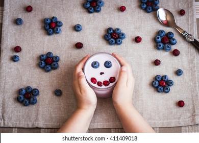 Healthy breakfast of yogurt and berries. Child creative breakfast. Top view, flat lay