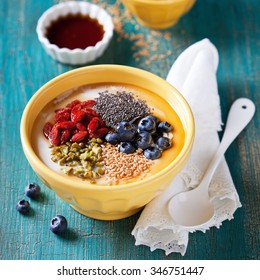 Healthy breakfast yogurt bowl with chia seeds, flax seeds, goji berries, blueberries, pistachio and maple syrup, selective focus
