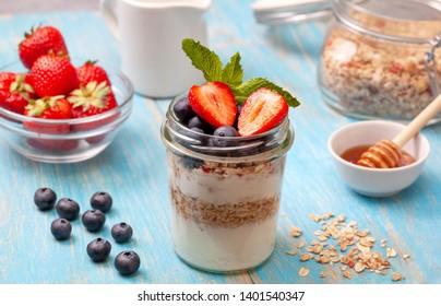 healthy breakfast. yogurt with granola, fresh berries on a blue wooden background