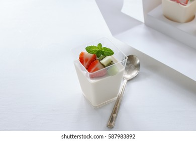 Healthy breakfast with yogurt and mixed fruit in plastic cup in box set.