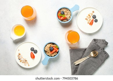 Healthy breakfast - yogurt with muesli and berries. A children's concept - persons of snowmen. Top view. Flat lay
