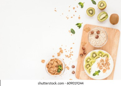 Healthy breakfast with yogurt, muesli, fresh green fruits, cereal, nuts on white background. Flat lay, top view.