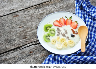 Healthy breakfast of yogurt, strawberries,banana and kiwi with chia seeds.