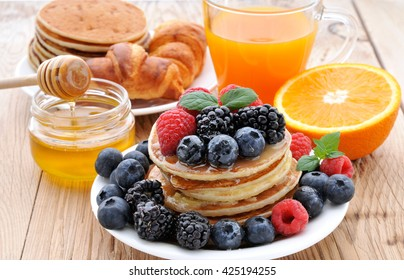 Healthy Breakfast.Pancakes with berries,fresh juice, croissants and honey