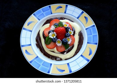 Healthy breakfest for good start, vanilla and chocolate puding with fruits and edible flowers