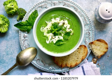 Healthy broccoli soup in a bowl over light blue slate, stone or concrete background.Top view with copy space.