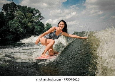 Healthy brunette female riding the wave on wakeboard lifting up a lot of splashes at the river