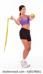 Healthy brunette woman with a tape measure and apple looking at camera while wearing violet and black gymnastic clothing, hair tied back, isolated
