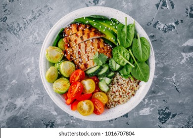 Healthy buddha bowl lunch with grilled chicken, quinoa, spinach, avocado, brussels sprouts, tomatoes, cucumbers  on dark gray background. Top view.
