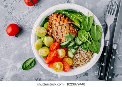 Healthy buddha bowl lunch with grilled chicken, quinoa, spinach, avocado, brussels sprouts, tomatoes, cucumbers  on dark grey background. Top view.