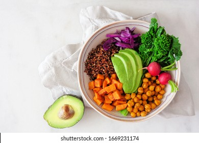 Healthy Buddha bowl with rapini, quinoa, sweet potato, chickpeas and avocado. Above view scene over a white marble background.