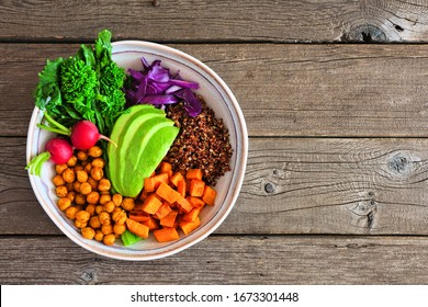 Healthy Buddha bowl with rapini, quinoa, sweet potato, chickpeas and avocado. Top view over a rustic wood background.