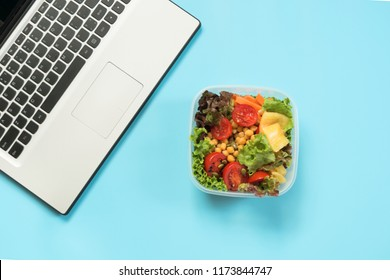 Healthy business lunch in office, salad for snack on blue. Top view with copy space. Concept proper nutrition. Office lunch. Take away lunchbox.