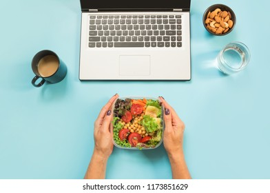 Healthy business lunch in the office, salad for snack, glass of water, almonds, cup of coffee on blue table. Top view with copy space. Concept proper nutrition. Lunchbox. Take away.