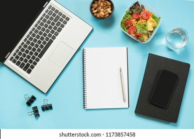 Healthy business lunch in office, salad for snack, almonds, water on blue. Top view with copy space. Concept proper nutrition. Lunchbox. Take away.
