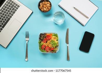 Healthy business lunch in office, salad for snack, almonds, water on blue table. Top view with copy space. Concept healthy nutrition. Lunchbox. To do list.