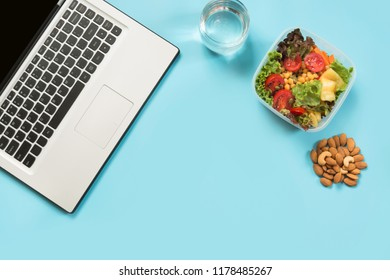 Healthy business lunch in office, salad for snack, almonds, water on blue. Top view with copy space. Concept proper nutrition. Lunchbox.