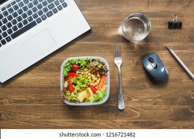 Healthy business lunch in office, salad, water on wooden table. Top view with copy space. Concept healthy nutrition for work. Lunchbox. Copy space.