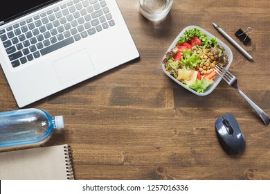 Healthy business lunch in office, salad, water on wooden table. Top view with copy space. Concept healthy nutrition. Lunchbox. Copy space.