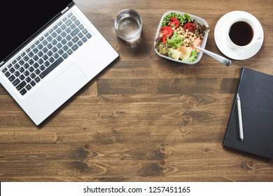 Healthy business lunch in office, salad, coffee on wooden table. Top view with copy space. Concept healthy nutrition. Lunchbox. Copy space.