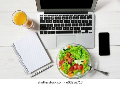 Healthy business lunch in office, top view of vegetable salad on white wooden desk near laptop computer keyboard. Snack at break time