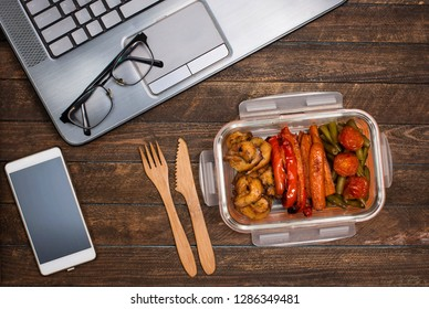 Healthy business lunch at workplace. Baked vegetables and chicken lunch box on working desk with laptop smartphone and glasses.