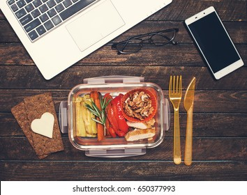 Healthy business lunch at workplace. Grilled vegetables and fried chicken lunch box on working desk with laptop smartphone and glasses.