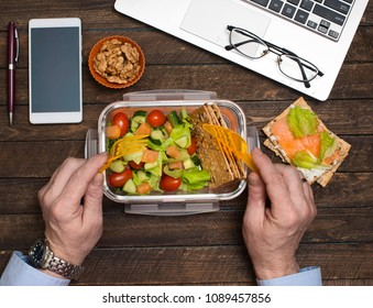 Healthy business lunch at workplace. Salad, salmon, avocado and bread crisps lunch box on working desk with laptop, smartphone, glasses and coffee.