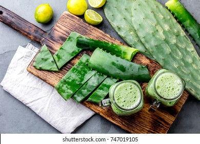 Healthy cactus nopales, aloe vera and lemon drink smoothie and ingredients on gray background. Top view.