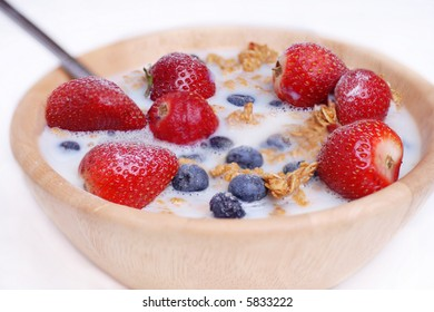 Healthy cereal breakfast, oats, blueberries and strawberry's with low fat skimmed milk.