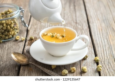 Healthy chamomile tea poured into white cup. Teapot and spoon, glass jar of daisy medicinal herbs.