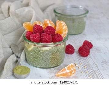 Healthy chia seeds pudding with green tea matcha and raspberries, orange on wooden table
