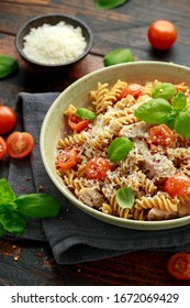 Healthy Chicken, fusilli pasta with tomatoes, basil and parmesan cheese. on wooden table.