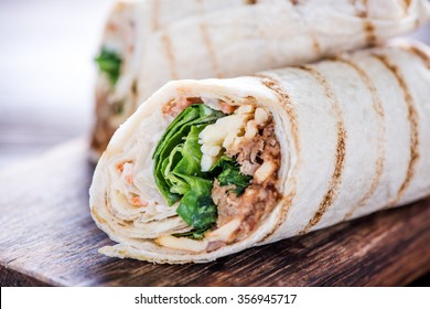 Healthy chicken grilled wrap, on wooden serving board