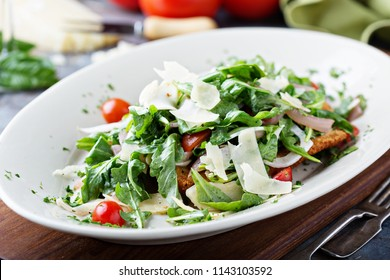 Healthy chicken parmesan topped with arugula, tomatoes and parmesan