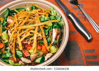 Healthy chicken salad with a mix of vegetables, cucumber, tomatoes, lettuce, kale, corn, and onions. Topped with tortilla wheat strips on a orange table cloth.