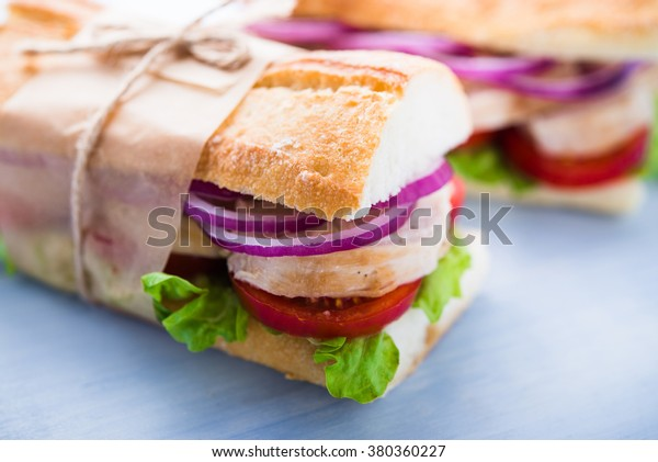 Healthy chicken sandwiches with lettuce salad, tomato and onion on blue wooden background close up. Healthy food.