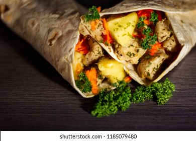 Healthy chicken wrap containing pineapple, carrot, tomato cubes and greenery