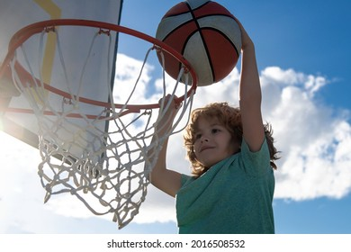 Healthy children lifestyle. Closeup face of kid basketball player making slam dunk.